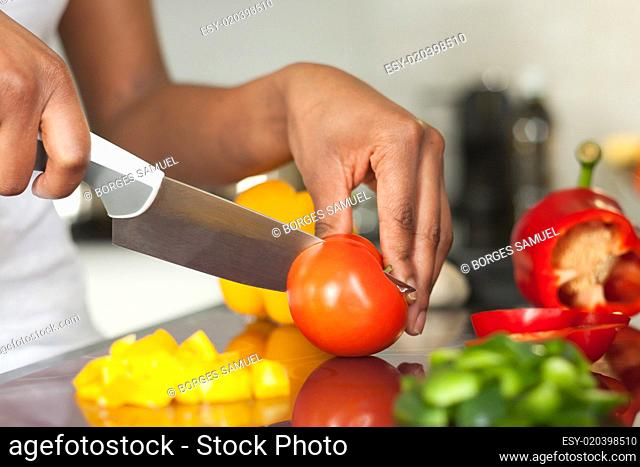 African American womans hand slicing a tomatoe