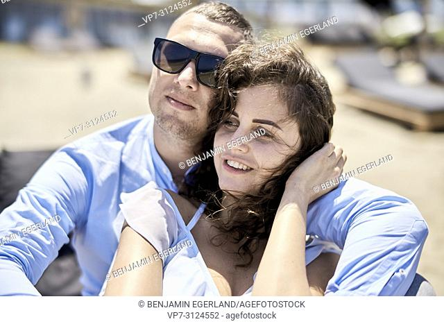 man embracing woman, on sunbeds, vacations, love, affair, sensual, couple, flirt, summer