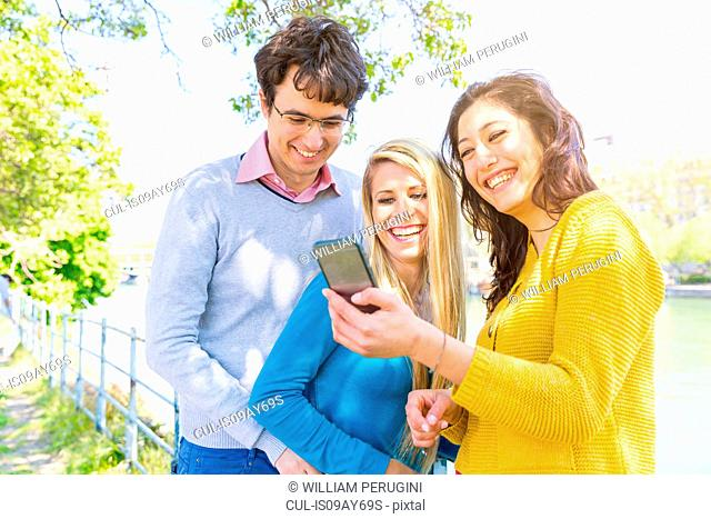 Friends by river looking at smartphone smiling