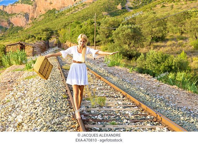 Young woman balancing on railroad
