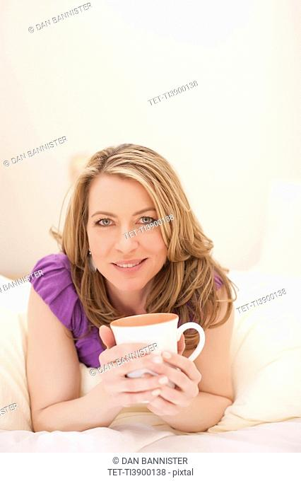 Woman lying down with a cup of coffee