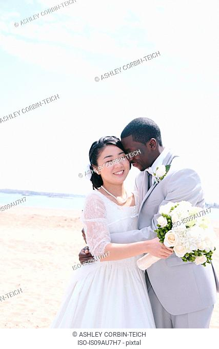 Bride and bridegroom on beach holding bridal bouquet hugging, smiling