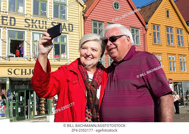Bergen Norway Bryggen retired tourist couple taking photo in front of colorful old wooden houses and smiling selfie MR-11