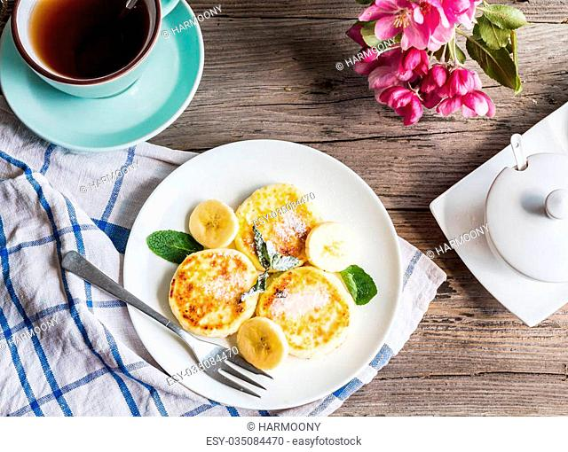 pancakes from cottage cheese with banana, powdered sugar and fresh mint, gray wooden background, breakfast