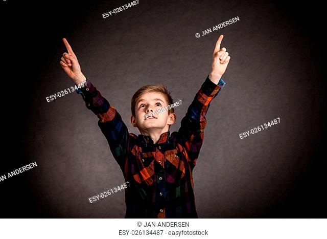 Half Body Shot of a Handsome Boy Pointing his Two Index Fingers Up Against Abstract Gray Background with Copy Space