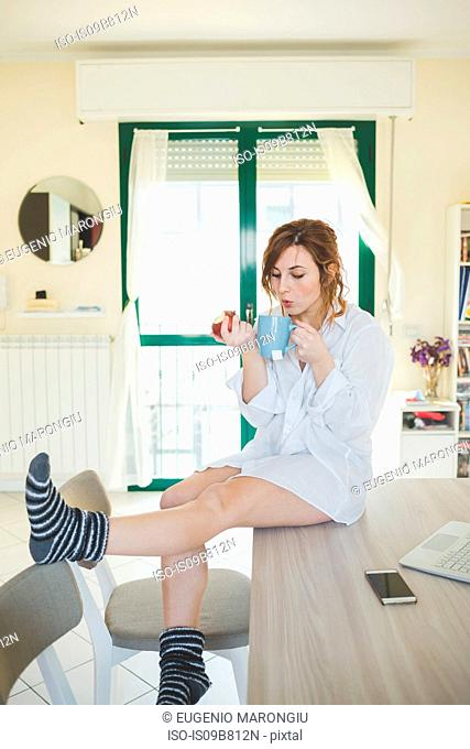 Young woman sitting on kitchen table blowing teacup and eating an apple