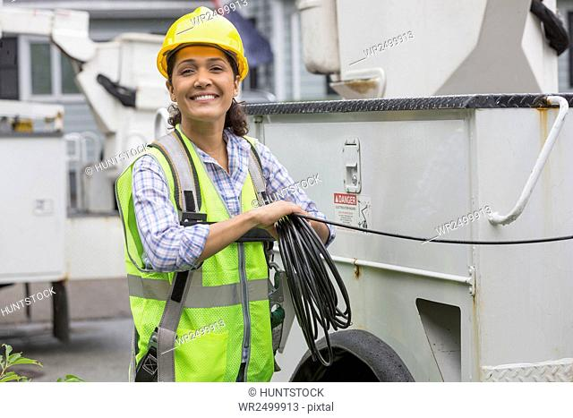 Portrait of happy Hispanic female utility worker holding cable by truck at site