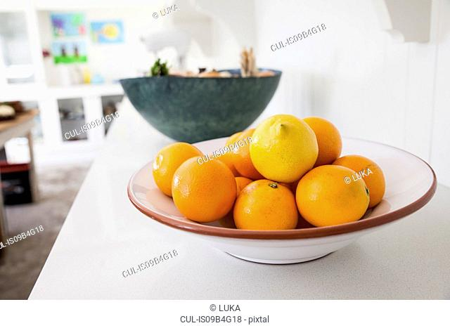 Bowl of fresh oranges on kitchen counter