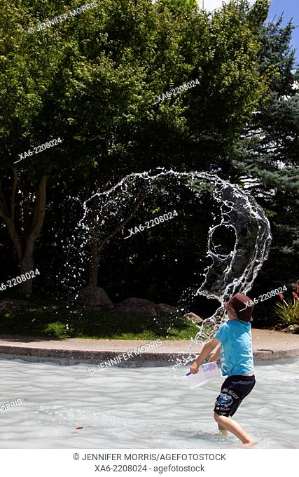 A child throws water into the air in a shallow pool