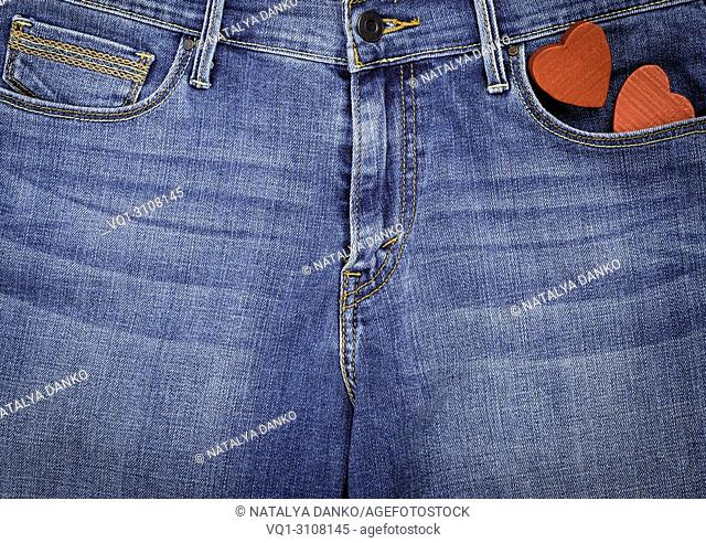 blue jeans and two red wooden hearts, full frame