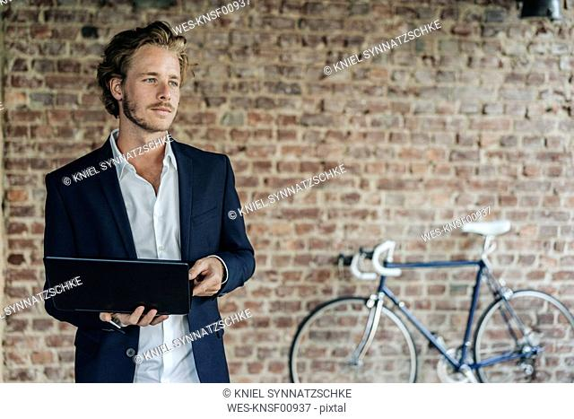 Businessman with laptop looking away