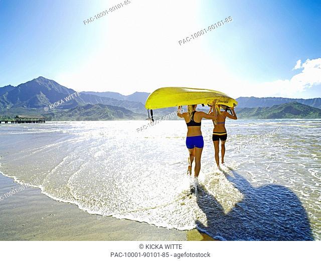 Hawaii, Kauai, Hanalei Bay, Two active young woman carrying a kayak into the ocean