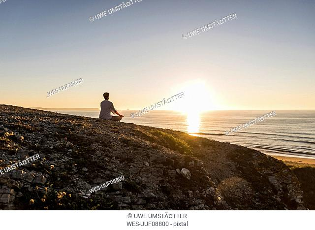 Back view of woman meditating on cliff at sunset