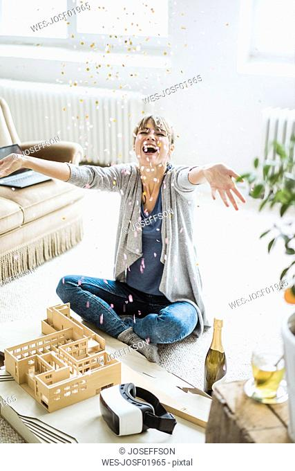 Confetti falling on happy woman in office with architectural model