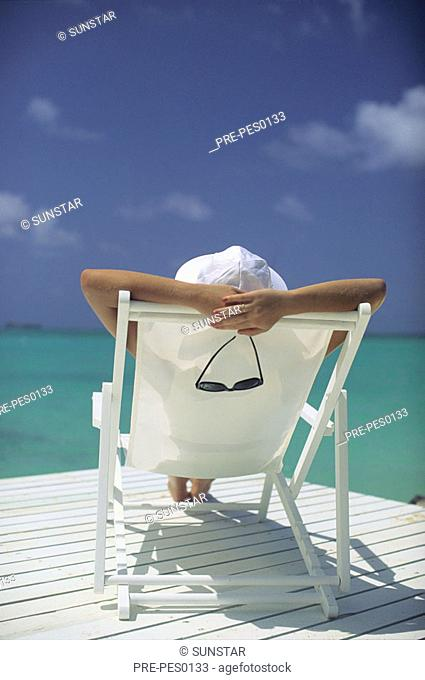 Woman sitting in a deck chair looking over the sea, holding sun glasses, view from behind