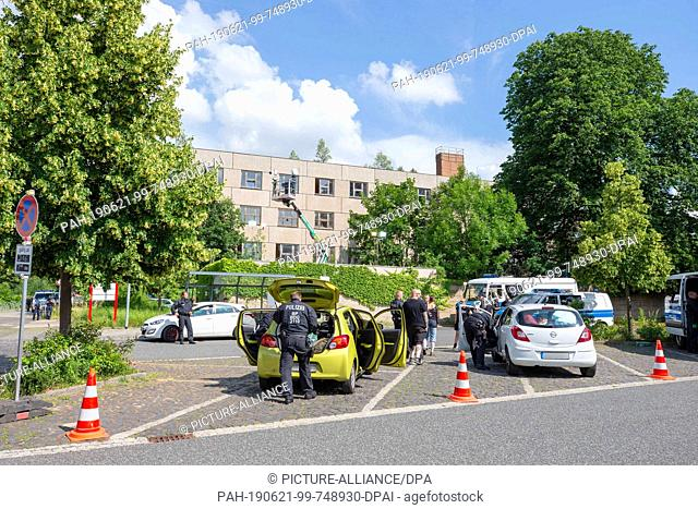 21 June 2019, Saxony, Ostritz: Police officers search people and their vehicles in a parking lot opposite the hotel where the so-called Shield and Sword...