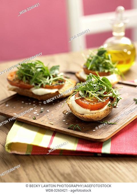 tostada de pan con mozzarella, tomate asado, rucula y hierbas aromaticas