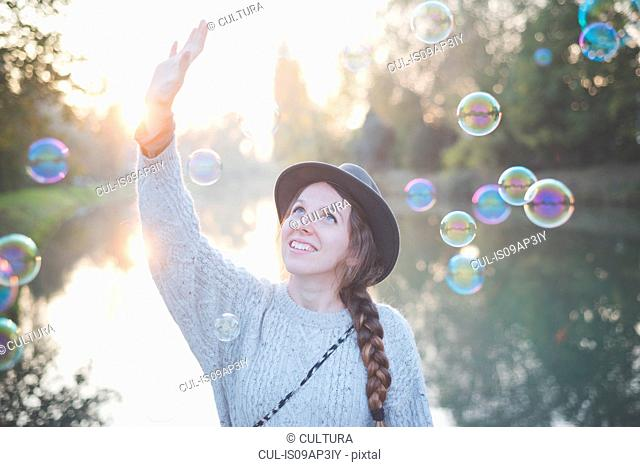 Young woman playing with bubbles