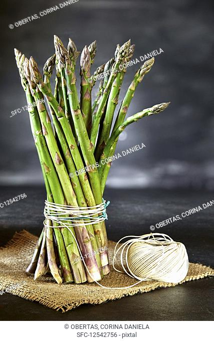 Bunch of asparagus tied with kitchen twine, on a piece of hemp sack