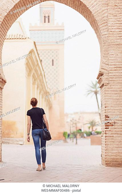 Morocco, Marrakesh, back view of woman looking at Kasbah Mosque