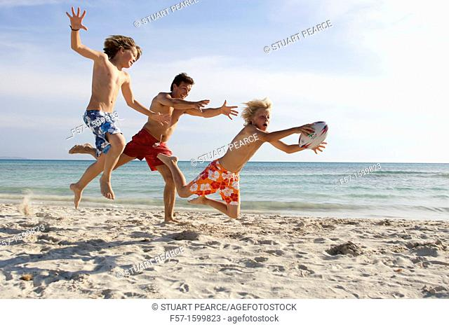 Father and sons playing ball on the beach