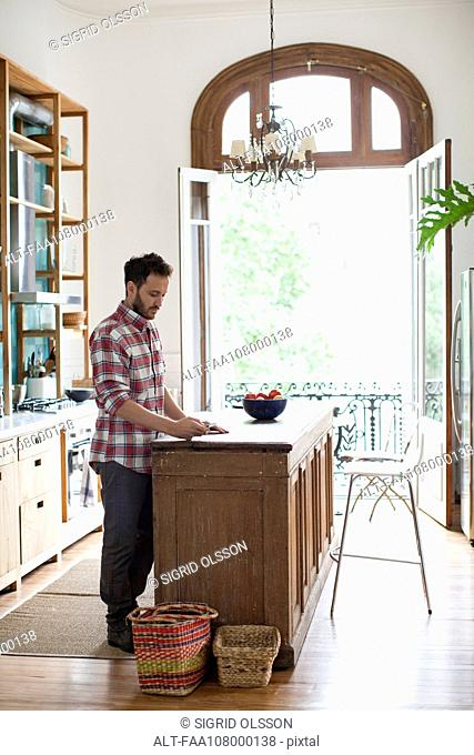 Man in home kitchen text messaging