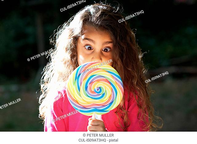 Portrait of girl crossing eyes with lollipop in front of her face in garden