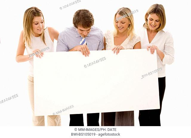 Four business people look at the blank sign they are holding