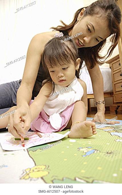 Mother and child drawing with crayons