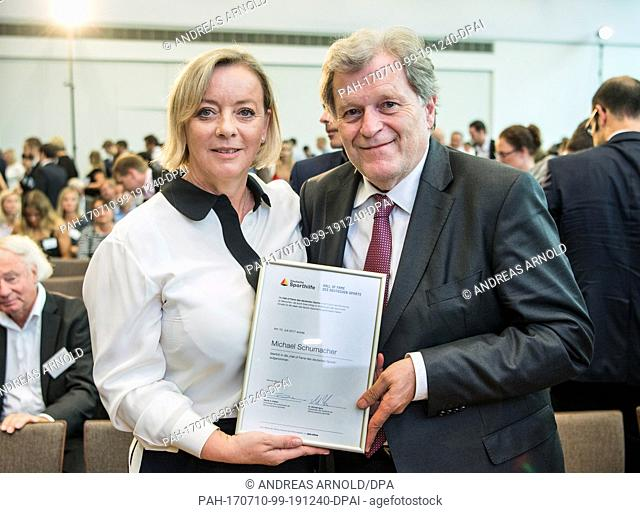 Sabine Kehm, Michael Schumacher's manager, and the former head of Mercedes motorsport Norbert Haug, hold the certificate for the Formula 1 racing driver in...