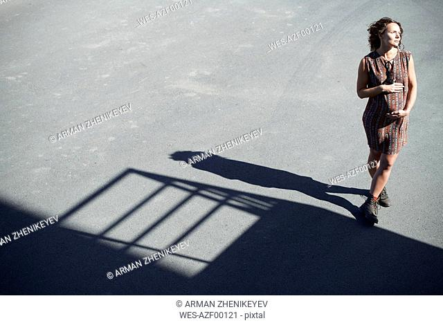 Pregnant woman standing on tarnac in sunlight