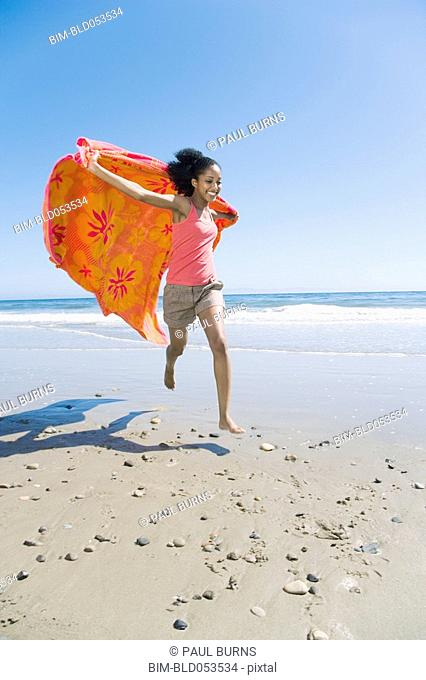 African woman running with beach towel