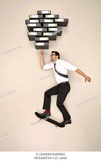 Businessman skateboarding balancing folders on his finger tip