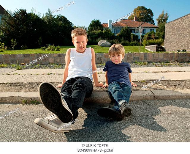 Brothers sitting together on sidewalk