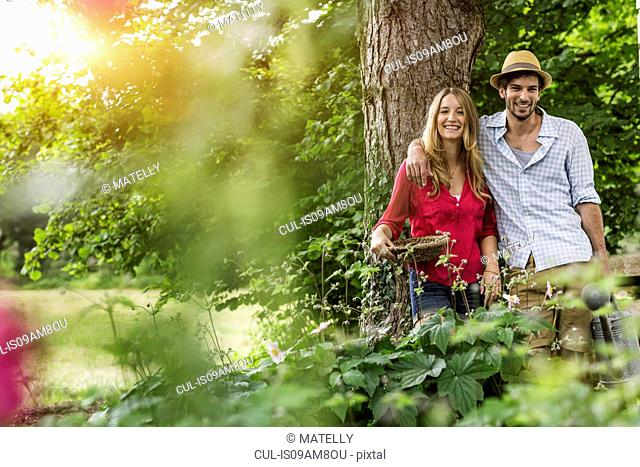 Portrait of young couple with flower basket in garden