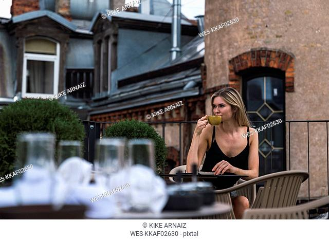 Young woman sitting on roof terrace drinking cup of coffee