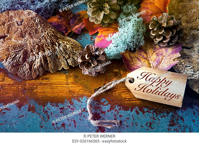 'Happy Holidays' written on wooden tag on wooden vintage board with leaves and pinecones