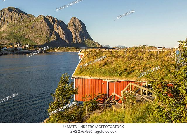 View over Reine with a Rorbuer and mountains, warm eveninglight, Reine, Lofoten Islands, Norway