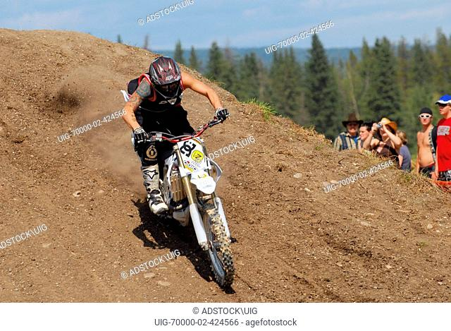 A motocross dirt bike rider lands a jump on a pile of dirt