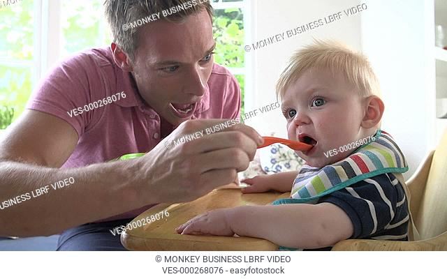 Father feeding baby son in high chair.Shot on Sony FS700 in PAL format at a frame rate of 200fps