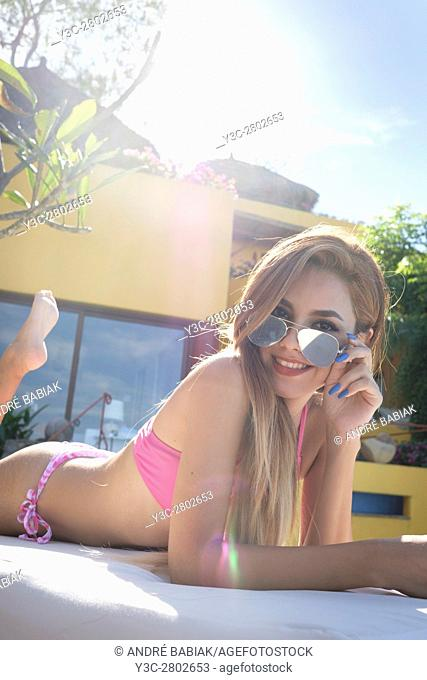 Female teenager in bikini looking cheeky over her sunglasses flirting with the camera, smiling while tanning