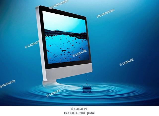 Still life with computer submerging in water