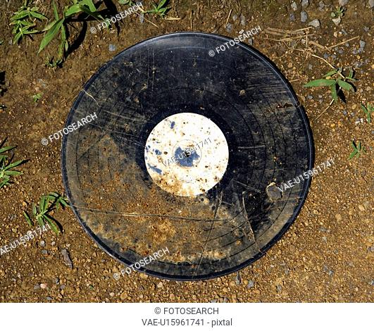 Dirty old record album on ground