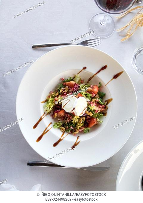 aerial view bowl round white plate salad with sliced tomato, lettuce, nut and pomegranate, cheese goat and Modena balsamic vinegar on white tablecloth next to...