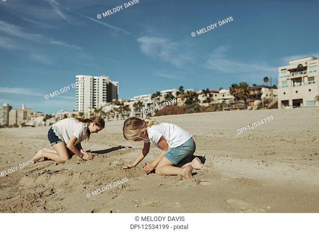 Two girls playing in the sand at the beach with condominium buildings in the background; Long Beach, California, United States of America