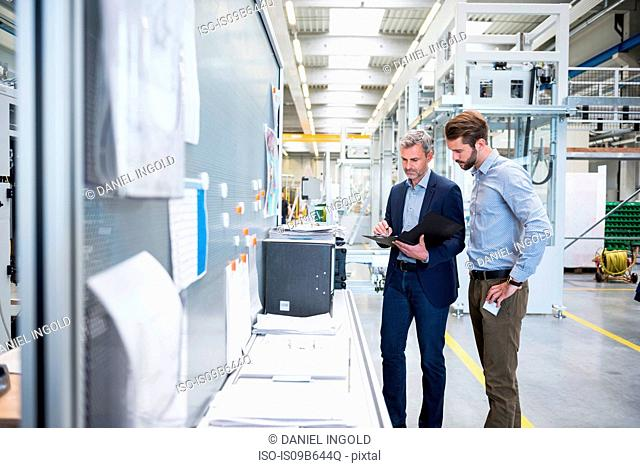 Businessmen with file in factory having discussion