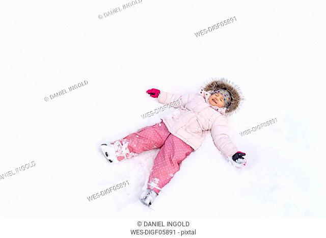 Cute little girl lying in snow in winter making a snow angel