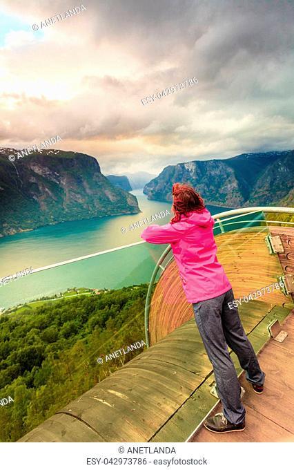 Tourist woman on Stegastein viewpoint enjoying Aurland fjord view in evening time, Sogn Og Fjordane, Norway