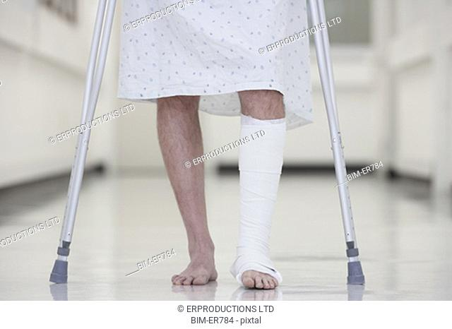 Close up of male with broken leg walking on crutches in hospital