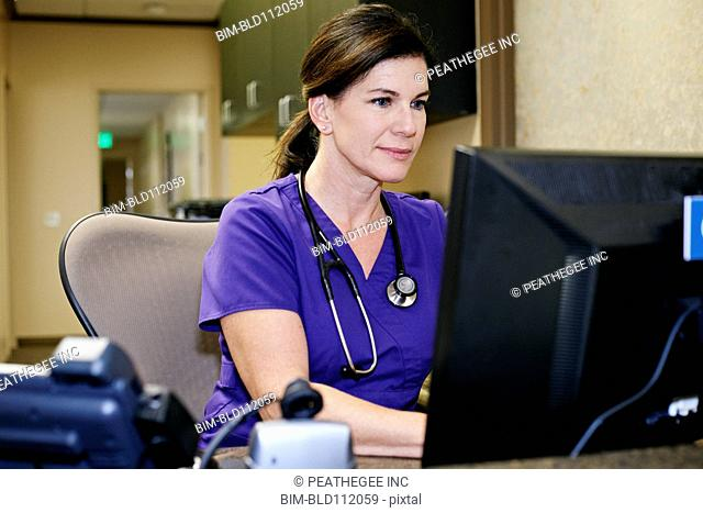 Caucasian nurse using computer in office